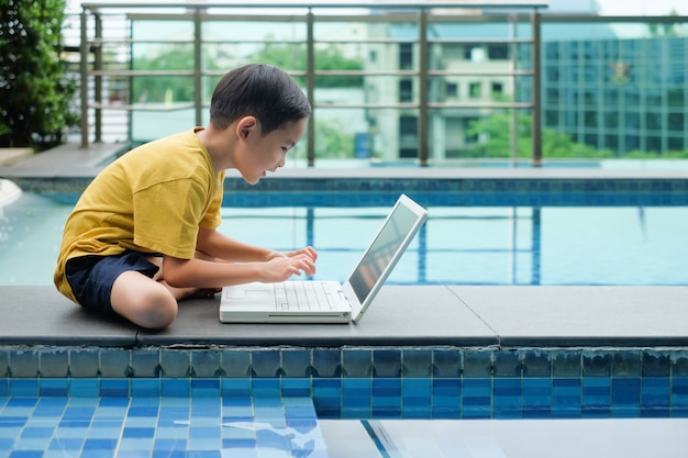 Asian boy child sitting side of pool and uses laptop for education Premium Photo