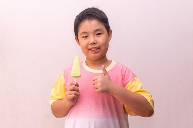 Азиатский мальчик ест портрет эскимо Premium Фотографии
