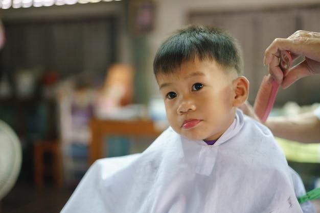 Asian boy getting hair cut by barber Premium Photo