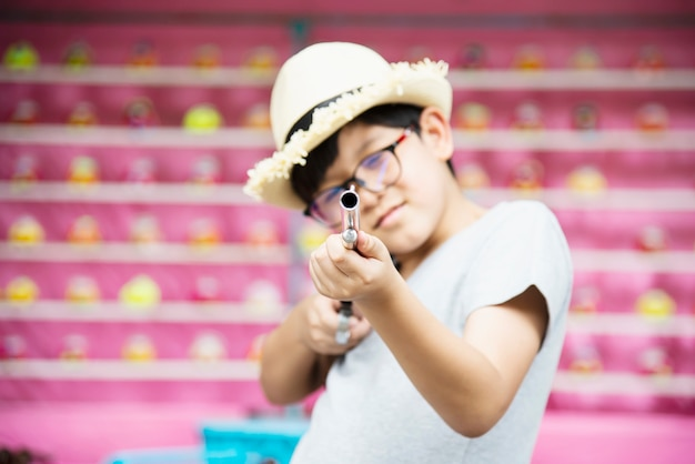 Asian boy happy playing doll gun shoot in local fun park festival event, people with happy activity Free Photo
