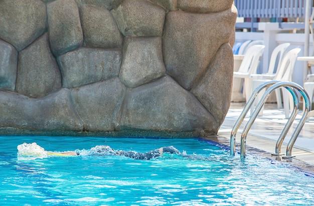 Asian boy holding foam swimming in the pool. Premium Photo