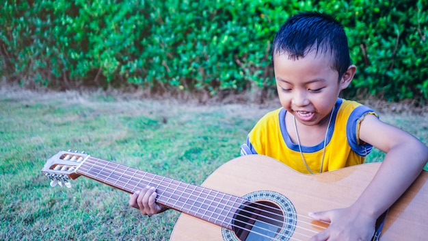 An asian boy is playing an acoustic guitar in a garden with green trees. Premium Photo