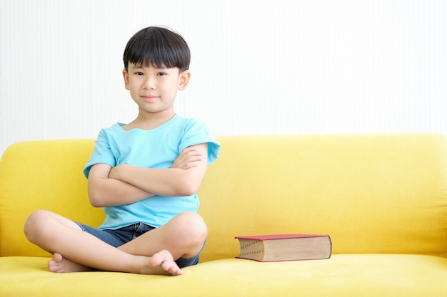 Asian boy is sitting on yellow sofa with big red book. Premium Photo