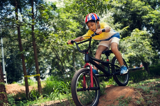 Asian boy is training for a happy mountain biking. Free Photo
