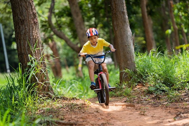 Asian boy is training for a happy mountain biking. Free Photo