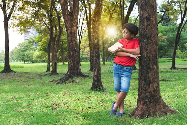 Asian boy leaning against the big tree in public park, a book in hand Premium Photo