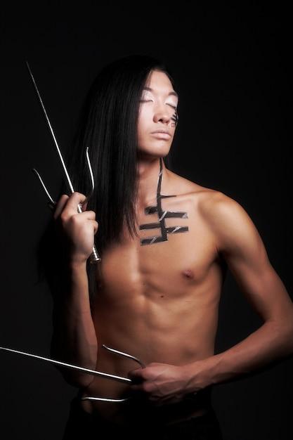 Азиатский мальчик на черном фоне Premium Фотографии