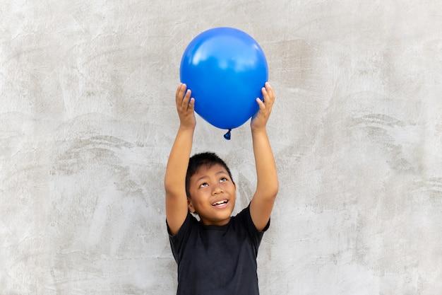 Asian boy play catches balloon on grey background. Premium Photo