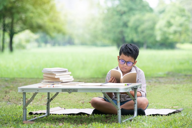 Asian boy reading a book with bored face while reading book in park Premium Photo