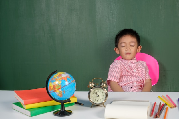 Asian boy sleeping in chalk board room Premium Photo