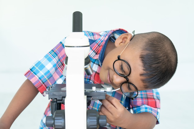 Asian boy use microscope in lab for research Premium Photo