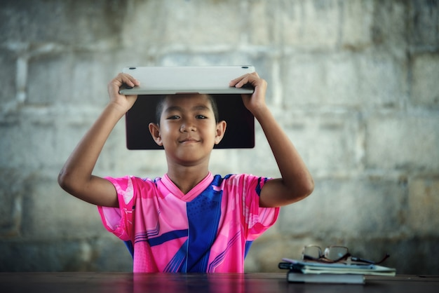 Asian boy using laptop on the table, come back to shcool Free Photo