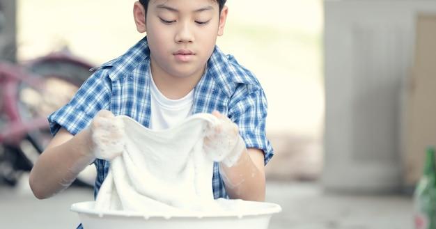 Asian boy washing his towel by hand. Premium Photo