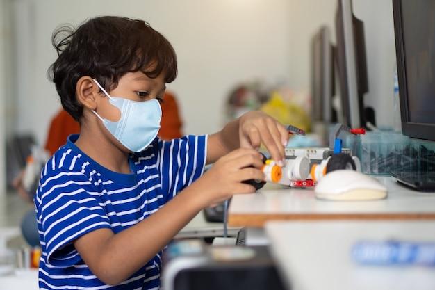 アジアの少年は、学校でコロナウイルス2019(covid-19)を防ぐためにフェイスマスクを着用しています。 Premium写真