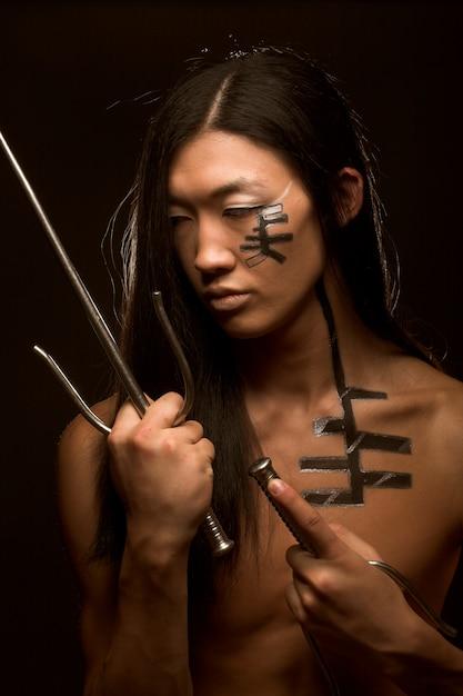 Азиатский мальчик с оружием Premium Фотографии