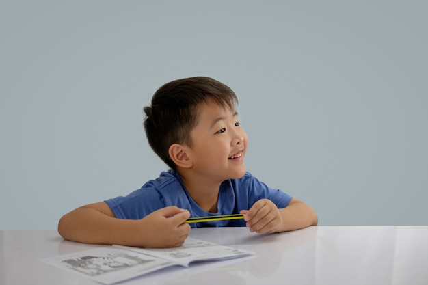 Asian boys are doing some writing on the book Premium Photo