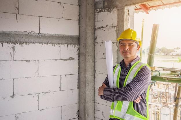 Азиатский деловой человек инженер-строитель в защитном шлеме и чертежах бумаги под рукой на строительной площадке Premium Фотографии