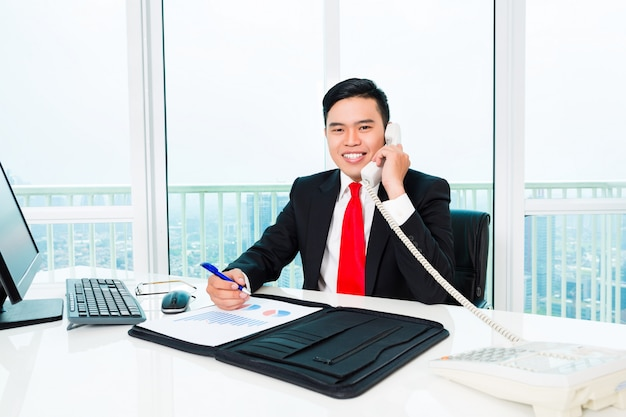 Asian business man telephoning in office controlling profit Premium Photo