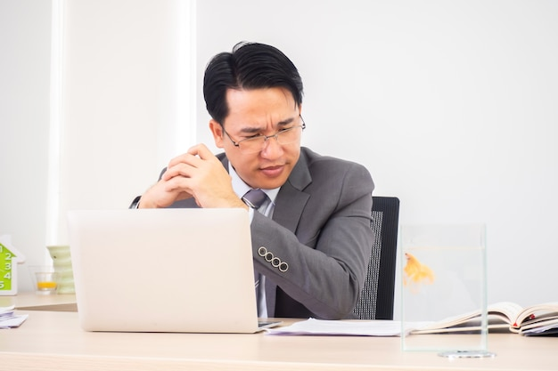Asian business man in working room. serious and thinking action. Premium Photo