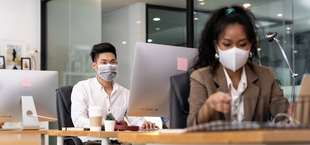 保護マスクを身に着けているオフィスで働くアジアのビジネスパーソン Premium写真