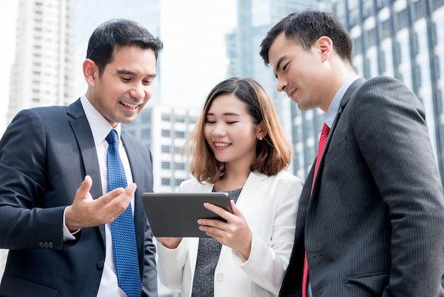 Asian business team discussing and sharing online work on tablet computer outdoors Premium Photo