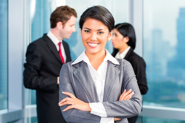 Asian business team in office, woman in front with skyline Premium Photo
