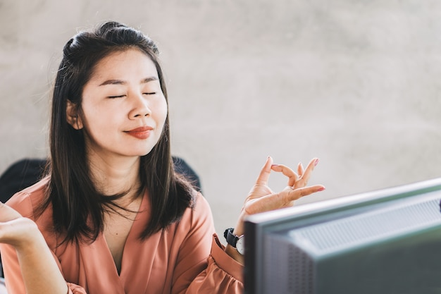 Asian business woman doing yoga at office desk Premium Photo