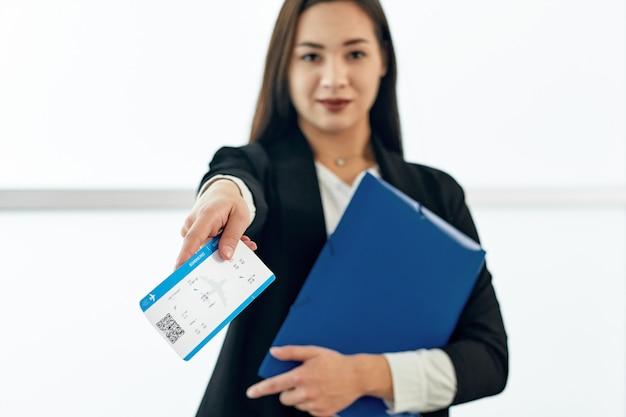空港で出発を待っているチケットを与えるアジアビジネス女性 Premium写真