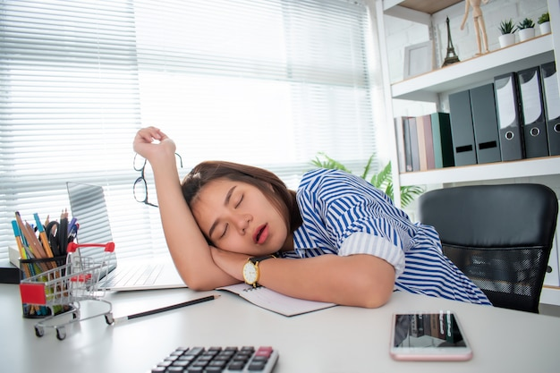 An asian business woman is sleeping due to exhaustion from hard work on her desk. Premium Photo