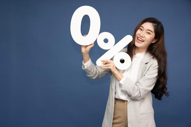 Азиатская деловая женщина показывает и держит 0% числа или ноль процентов, изолированных на темно-синей поверхности. Premium Фотографии