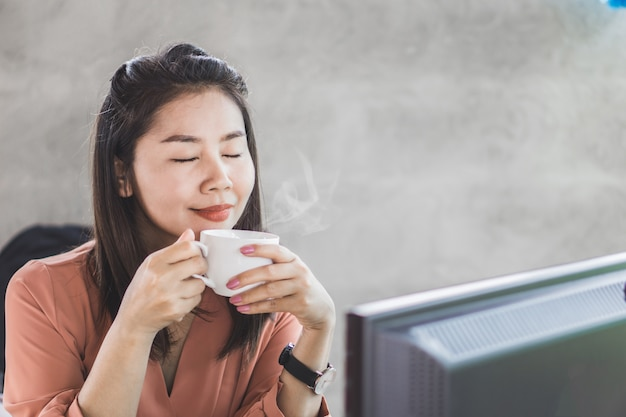 Asian business woman smelling cup of coffee Premium Photo
