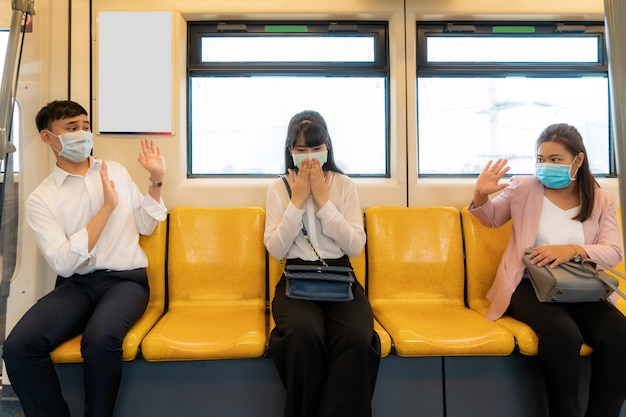 Asian business woman wearing mask sneezing or coughing in subway ...