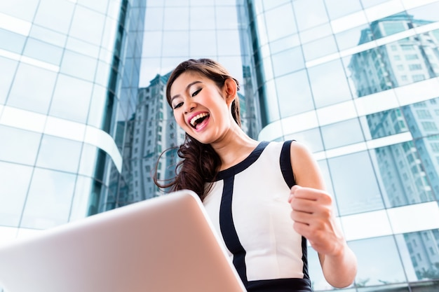 Asian business woman working outside on computer Premium Photo