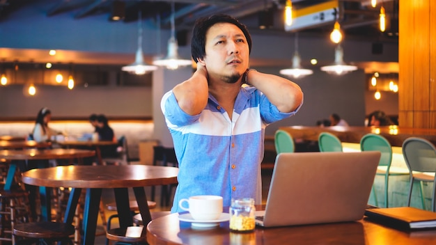 Asian businessman in casual suit working which have symptom is neck pain, backache, headac Premium Photo