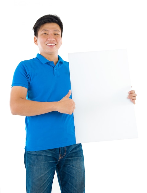 Asian businessman holding a blank card board with copy space, standing on plain background. Premium Photo