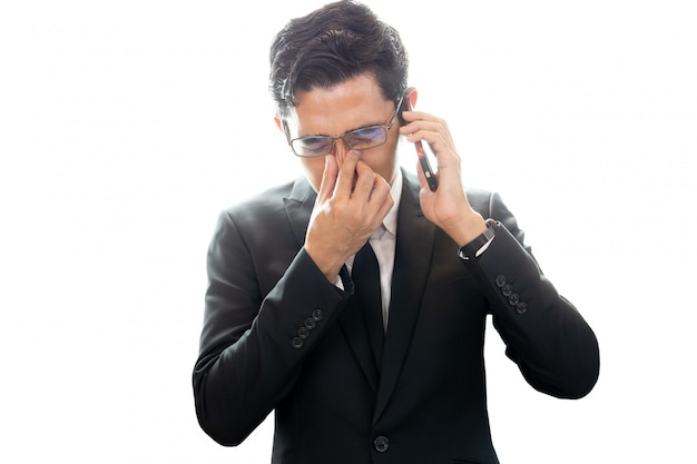 Asian businessman looking depressed while talking on cellphone isolated. Premium Photo