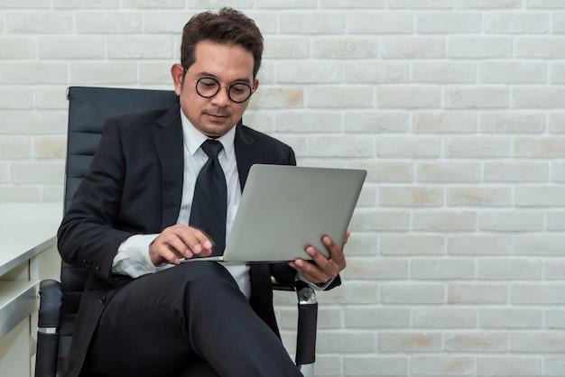 Asian businessman sitting on the working on laptop. Premium Photo