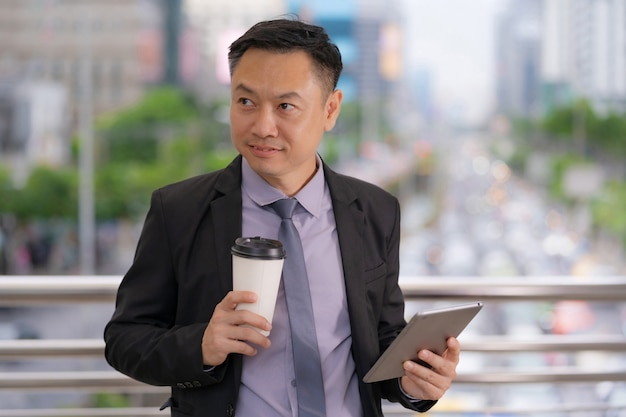 Asian businessman standing and holding digital tablet with business office buildings in the city Premium Photo