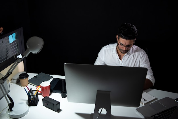 Asian businessman staying overtime late at night working in the office Premium Photo