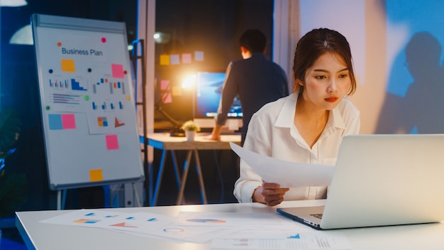 아시아 사업가는 컴퓨터를 끄고 작은 현대 홈 오피스 밤에 야근을 마치고 퇴근 할 때에도 여전히 일하는 동료에게 작별 인사를합니다. 동료 파트너십 개념. 무료 사진