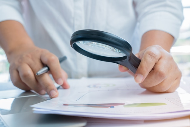 Asian businessman use magnifying glass scanning documents for checking investigate Premium Photo