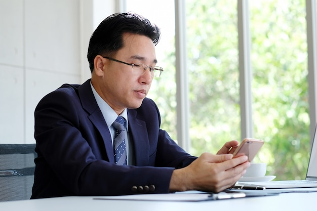 Asian businessman using phone while working at office, ceo business asian man with smart phone for communication while sitting in office, people business and technology Premium Photo
