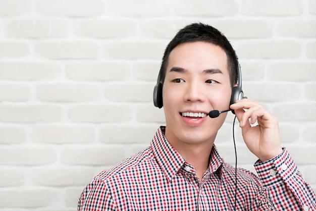 Asian businessman wearing microphone headset as a telemarketing customer service agent, call center job concept Premium Photo