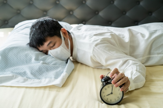 Asian businessman wearing surgical mask sleeping on the bed with alarm clock Premium Photo