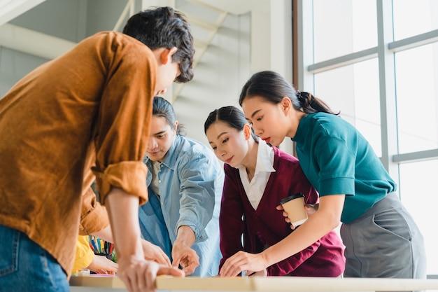 アジアのビジネスマンやビジネスウーマンがクリエイティブなウェブデザイン計画アプリケーションに関するブレーンストーミングのアイデアを会議し、小規模オフィスで一緒に働く携帯電話プロジェクトのテンプレートレイアウトを開発しています。 無料写真