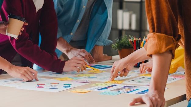 Uomini d'affari asiatici e donne d'affari che incontrano idee di brainstorming sull'applicazione di pianificazione del web design creativo e sviluppo del layout del modello per il progetto di telefonia mobile che lavorano insieme in un piccolo ufficio. Foto Gratuite