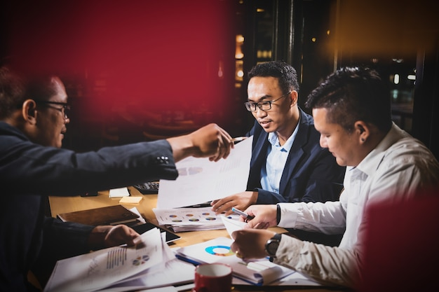 Asian businessmen discussing work sitting in office conference room at night scene Premium Photo
