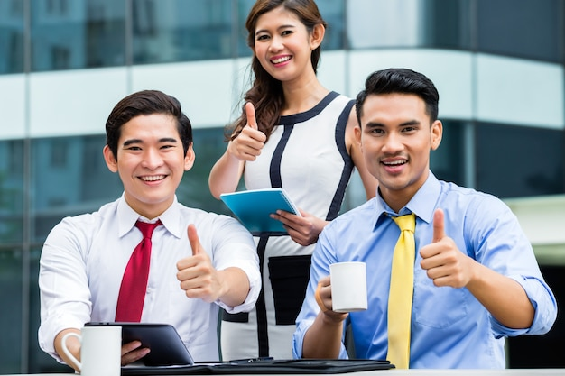 Asian businesspeople working outside with coffee Premium Photo