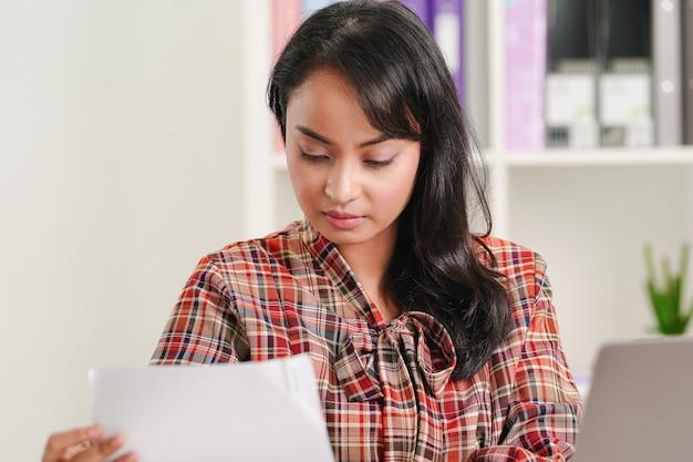 아시아 사업가 사무실에서 그녀의 직장에서 비즈니스 서류에 초점을 맞추고 있습니다. 재무 보고서 개념 분석. 프리미엄 사진