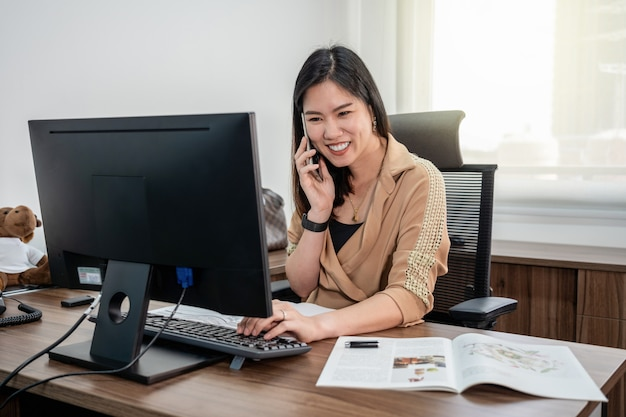 Asian businesswoman in formal suit writing and working with computer and mobile in office Premium Photo